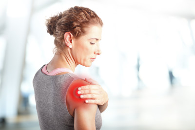 Lady holding her shoulder in pain